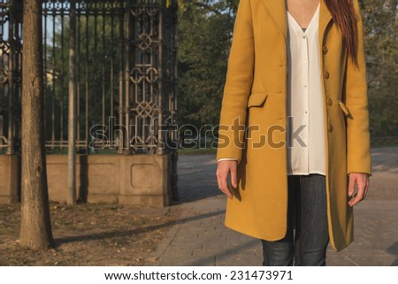 Detail of girl with yellow coat posing in a city park - stock photo