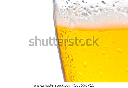 detail of glass of fresh beer with drops on white background, with space for text