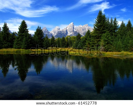 Detail of Grand Tetons Mountains with blue sky with relfection in river