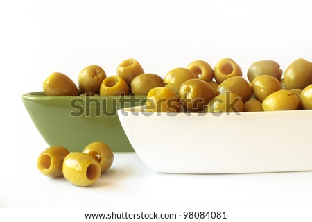 Detail of green olives in two ceramic bowls on white background - stock photo