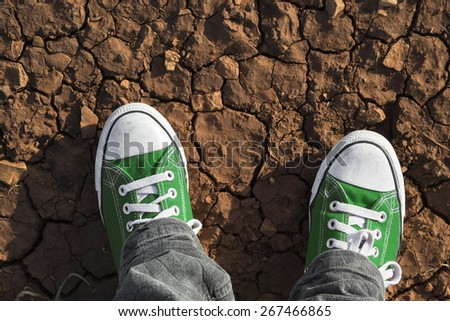 Detail of green trainers on dry ground - stock photo