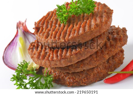 detail of grilled burgers with onion and piece of chili pepper