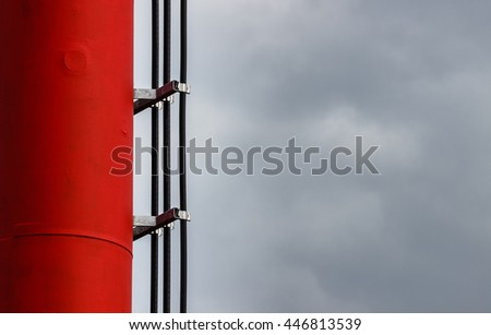 Detail of GSM tower (telecommunication antenna, transmitter) with vertical cable lines, cloudy sky. - stock photo