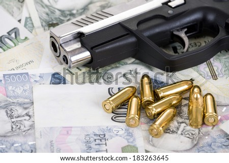 detail of gun with bullet on czech banknotes background - stock photo