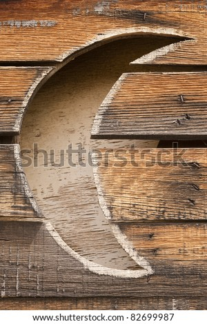 Detail of half-moon on door of outhouse. Vertical shot.