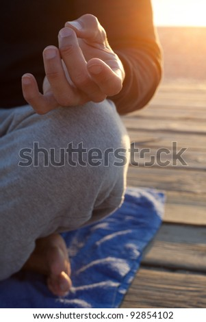 Detail of hand and kneel in yoga posture. - stock photo
