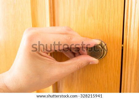 detail of hand is locking the latch of the wooden door  - stock photo
