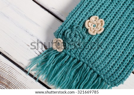 Detail of handmade knitted scarf.Wool scarf on a wooden background. - stock photo