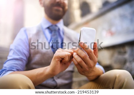 Detail of handsome hipster modern businessman using smart phone in the city - stock photo