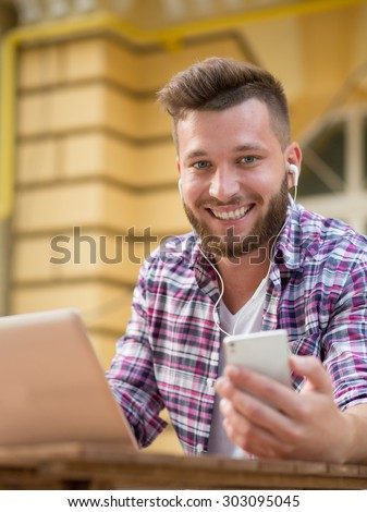 Detail of handsome hipster modern businessman using smart phone in the city. Smiling man in earphones working outdoors with laptop.