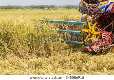 Detail of harvester machinery, tractor at farm with combine collecting mature grain crops - stock photo