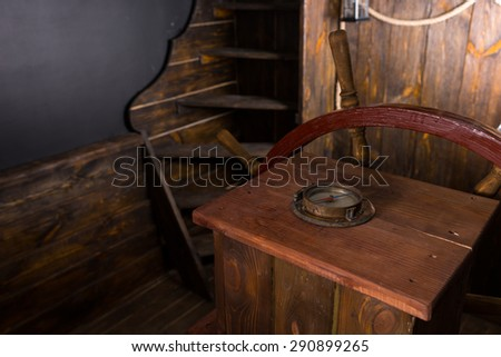 Detail of Helm of Antique Wooden Ship with Compass and Steering Wheel on Deck - stock photo