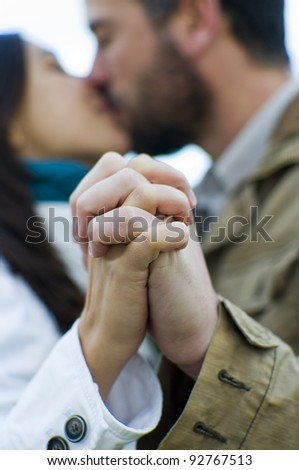 Detail of holding hands and couple kissing in the background - stock photo