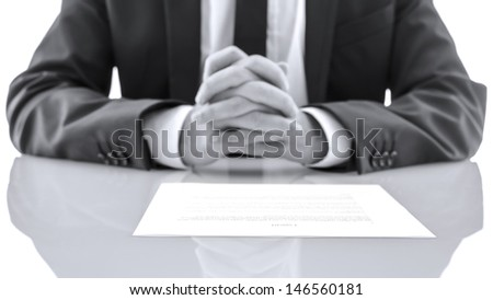 Detail of lawyer sitting at white desk with his hands together. Giving advice concept. - stock photo
