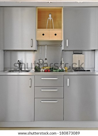 detail of little modern kitchen with vegetables on the worktop - stock photo