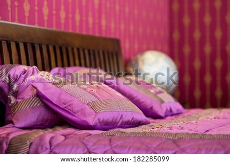 Detail of magenta cushions on the bed in beautiful colored bedroom - stock photo