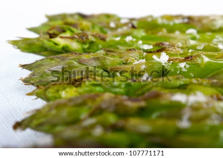 Detail of Maldon salt grains over grilled asparagus served on a glass dish that transparent the tablecloth - stock photo