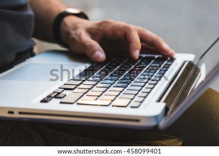 Detail of male hands working on laptop