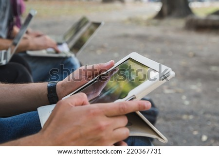 Detail of male hands working on white tablet - stock photo