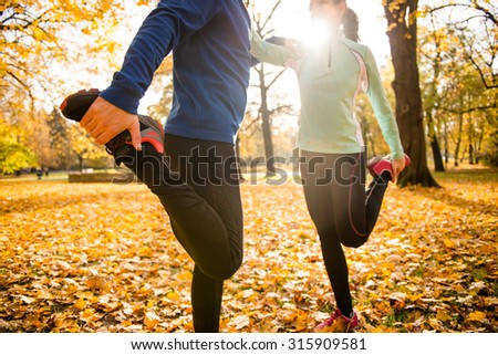 Detail of man and woman stretching legs before jogging in autumn nature - stock photo