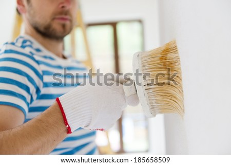 Detail of man painting the walls of new home with paintbrush - stock photo