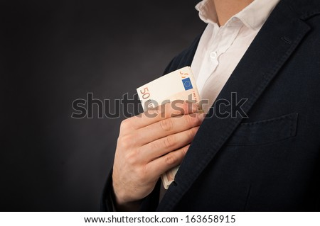 Detail of man's hand with euros banknotes against black background. - stock photo