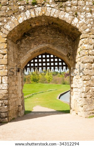 Detail of medieval stone castle gate, with grass and mote in the background - stock photo