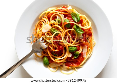 Detail of messy spaghetti with fork, tomato sauce, basil and cheese. Isolated on white from above.