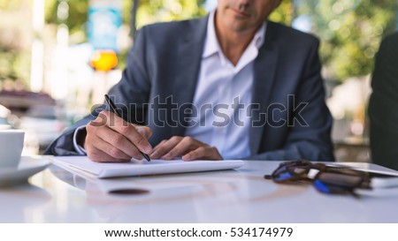 concentrate middle age businessman portrait writing stock photo  detail of middle age businessman portrait writing an essay outdoors in rome