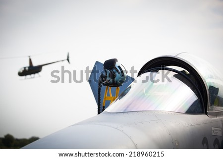Detail of military fighter/interceptor/jetplane cockpit with pilot's oxygen mask and helmet, ready to take off in case of terrorist attack (helicopter in background, colorful image) - stock photo
