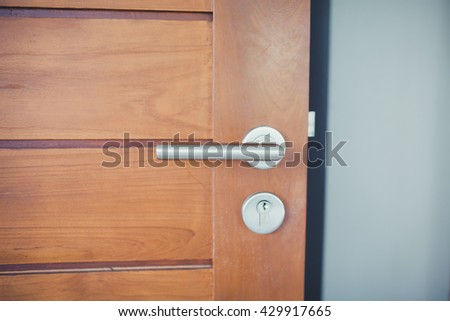 Detail of Modern style metallic door handle on wooden door