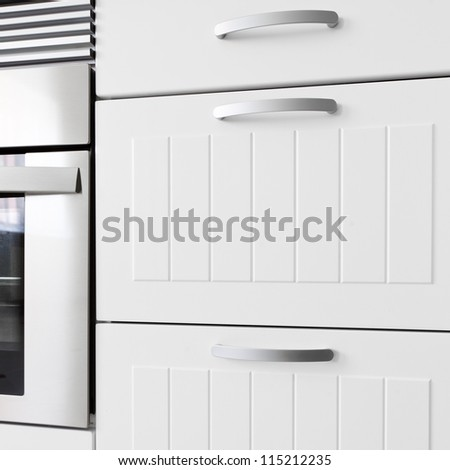 Detail of modern white kitchen. Drawers and oven. - stock photo