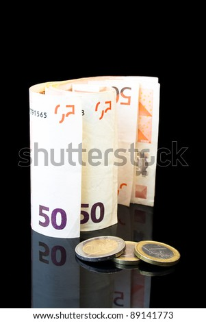 detail of money roll with euro coins on black background - stock photo