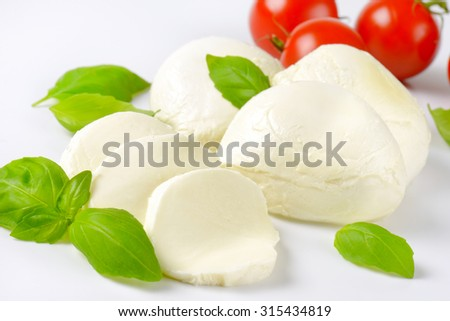 detail of mozzarella, cherry tomatoes and fresh basil - ingredients for caprese salad - stock photo