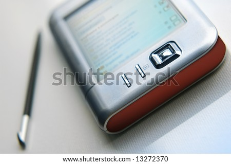 Detail of multimedia device. PDA and stylus. - stock photo