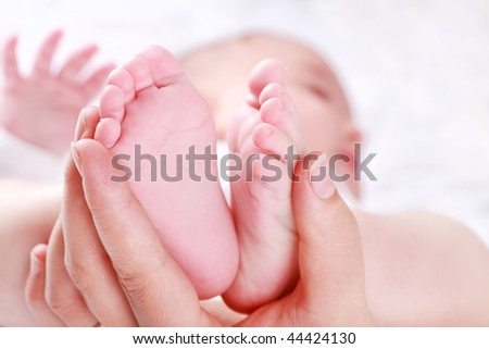 Detail of newborn's feet in mother's hands - shallow DOF