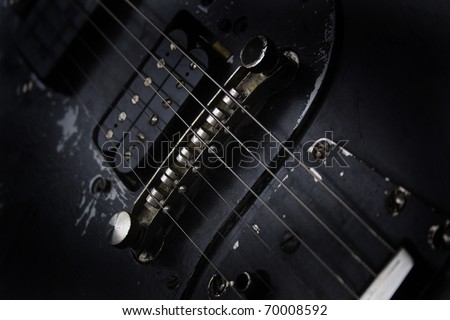 detail of old black guitar - stock photo