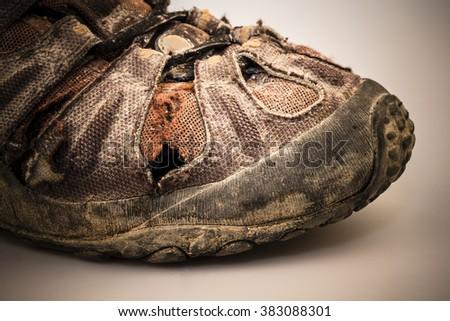 detail of old damaged hike shoe on white background - stock photo