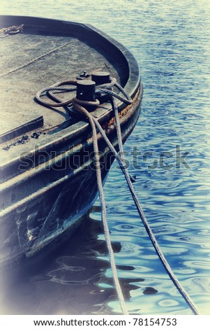 Detail of old fishing boat tied with rope at seacoast - stock photo