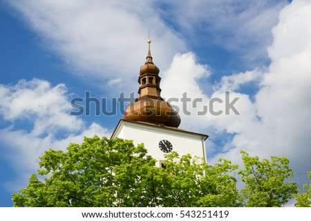 Detail of old historical architecture - baroque tower with cupola, spire and clock. In front of building is green tree during spring or summer