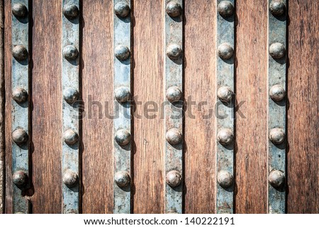 Detail of old solid door. Striped wood and metal door with metallic rivets looking worn and grungy. Part of ancient castle or fortress. Abstract backgrounds and wallpapers. - stock photo