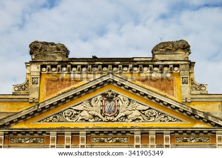 Detail of old Timisoara building on Piata Unirii (Square of Union) with relief of griphones and coat-of-arm with W symbol on it - stock photo