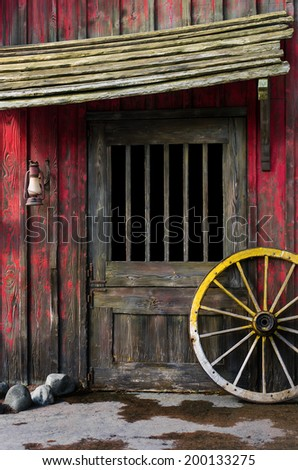 Detail of old wagon wheel next to a wooden wild west typical house - stock photo