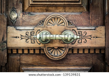 Detail of old wooden door with horizontal metal handle on board with carved pattern and keyhole over it. Dark brown solid front door in vintage and antique style. Exterior and facade. - stock photo