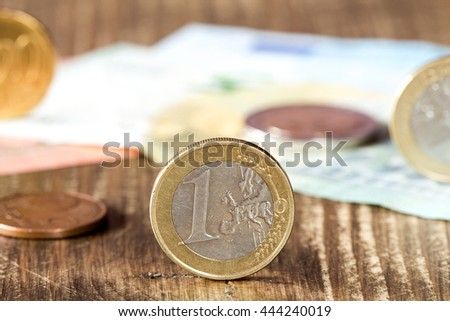 Detail of one euro coin, other euro coins and notes in background - stock photo