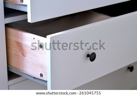 Detail of open white laminated drawer with brass handle - stock photo