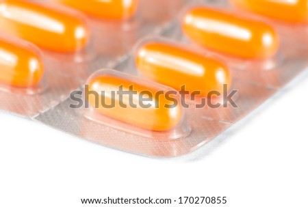 detail of orange pills packed in blister on white table - stock photo