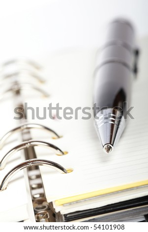 Detail of pen and opened agenda with very shallow depth of field - stock photo