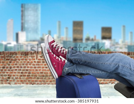 detail of person resting with legs over the baggage at the terrace of  - stock photo