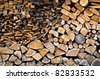 Detail of piled firewood trunks and planks - stock photo